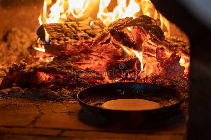 烹调在壁炉 在平底锅的薄煎饼在烤箱的火油煎 免版税库存照片