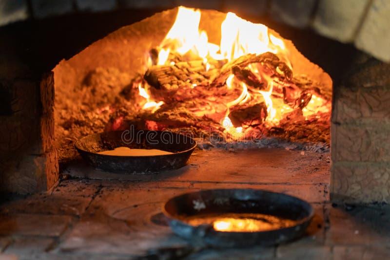 烹调在壁炉 在平底锅的薄煎饼在烤箱的火油煎 免版税库存图片
