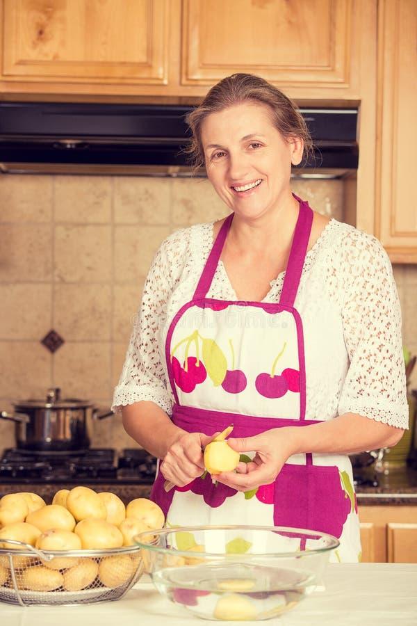 烹调在她的厨房里的微笑的妇女 免版税库存图片