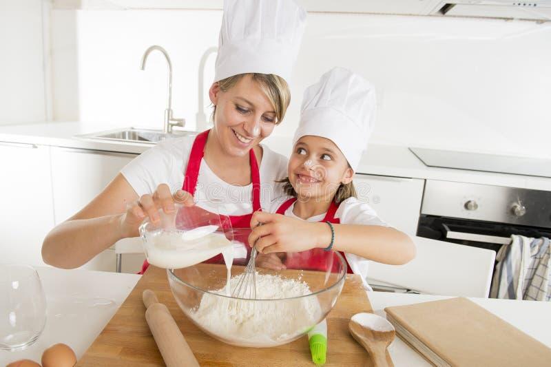 年轻烹调在家一起烘烤的母亲和小甜女儿厨师帽子的和围裙厨房 免版税库存图片