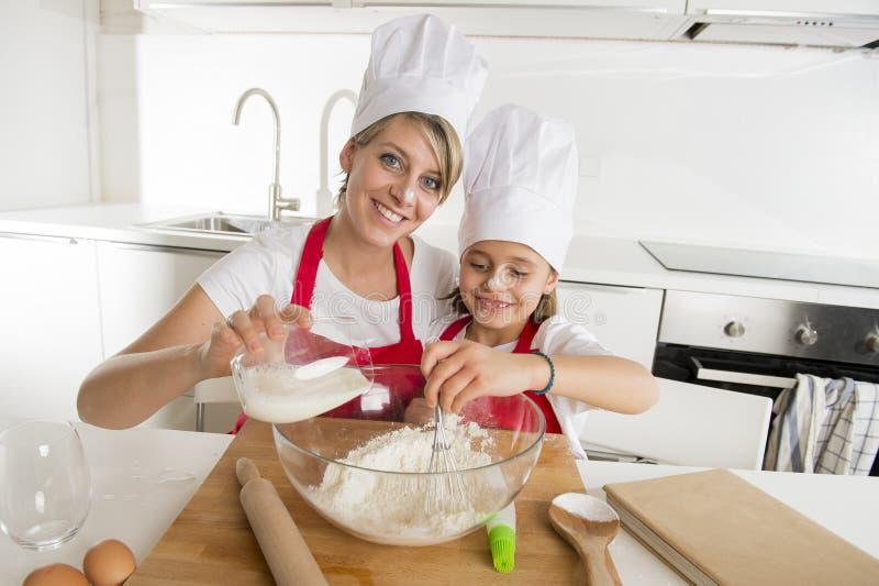 年轻烹调在家一起烘烤的母亲和小甜女儿厨师帽子的和围裙厨房 免版税库存照片