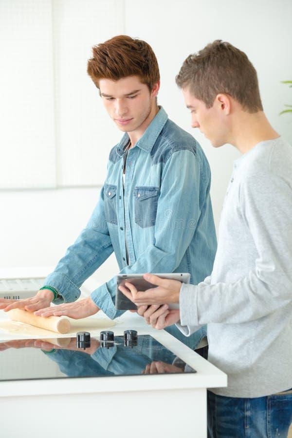 烹调在家庭厨房里的两个年轻人 库存照片