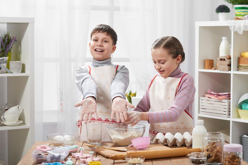 烹调在家庭厨房里的女孩和男孩 儿童展示手用面粉 免版税库存图片