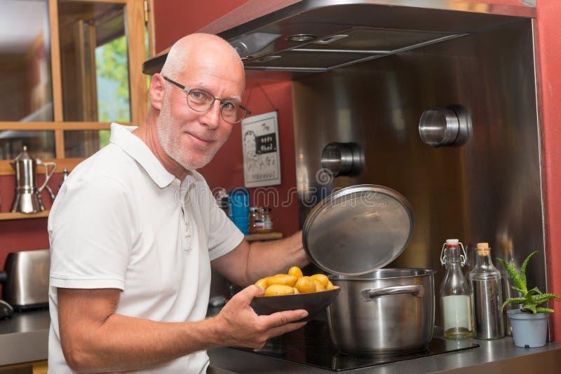 烹调在家庭厨房里的成熟英俊的人 库存照片