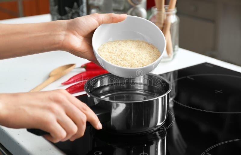 烹调在平底深锅的妇女米在火炉,特写镜头 库存照片