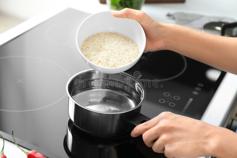 烹调在平底深锅的妇女米在火炉,特写镜头 免版税库存图片