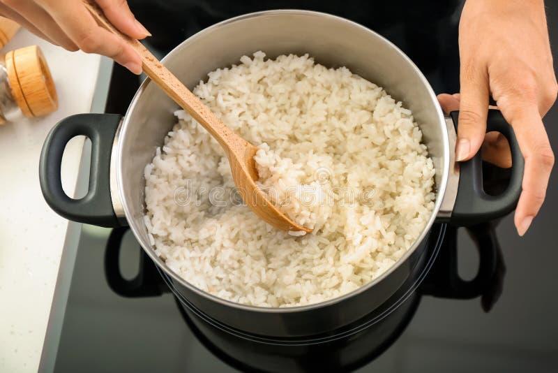 烹调在平底深锅的妇女米在火炉 免版税库存照片