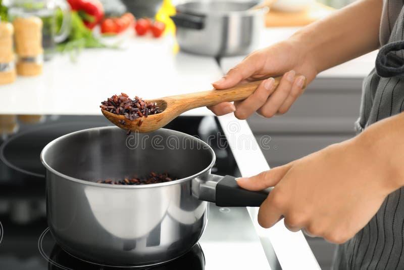 烹调在平底深锅的妇女米在火炉 库存照片