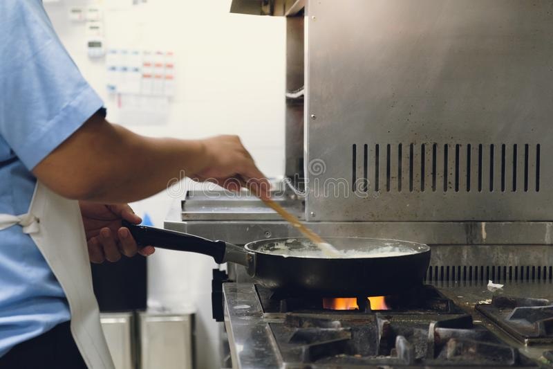烹调在平底锅的食物由在煤气炉的厨师手 免版税库存照片
