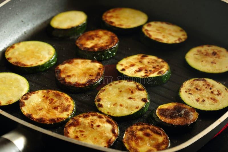 烹调在平板炉煎锅的切的绿皮胡瓜夏南瓜 免版税图库摄影