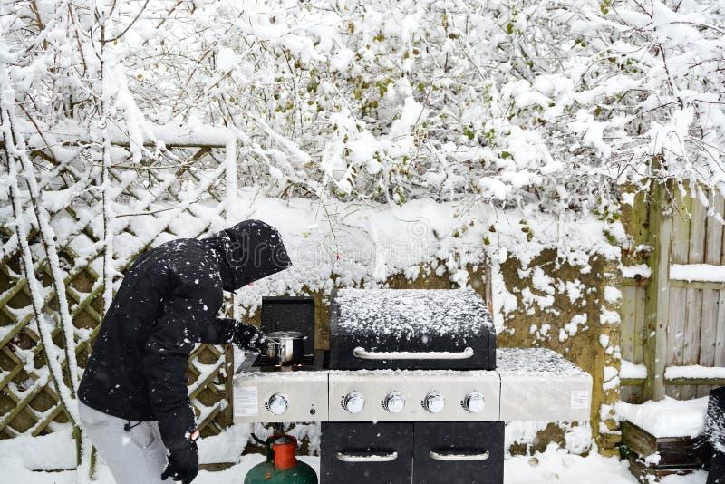 烹调在暴风雪的烤肉的一个人 库存图片