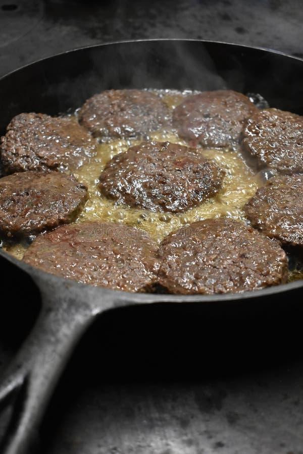烹调在木火炉的铸铁长柄浅锅的汉堡包 免版税图库摄影