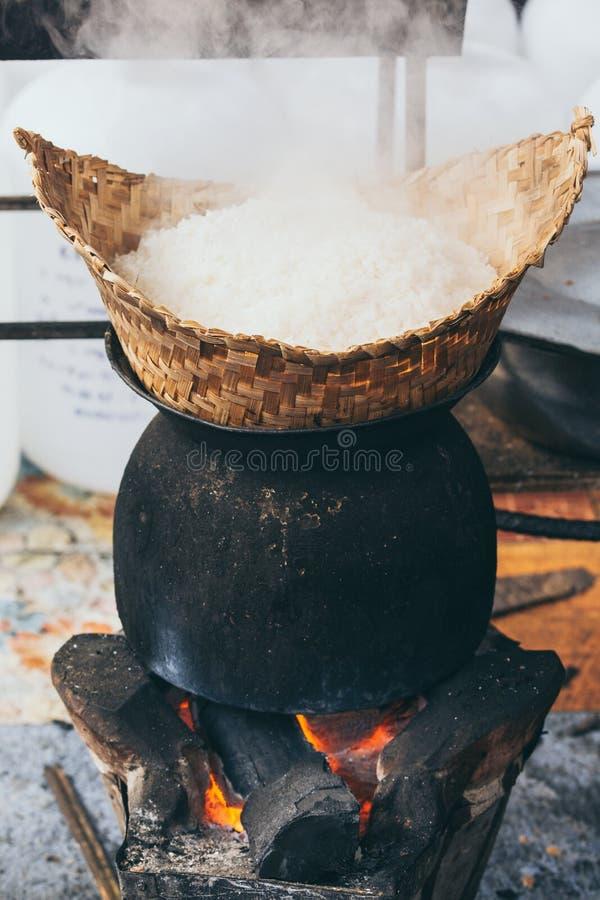 烹调在木灼烧的火炉的白色老挝蒸汽米在琅勃拉邦,老挝 免版税库存照片
