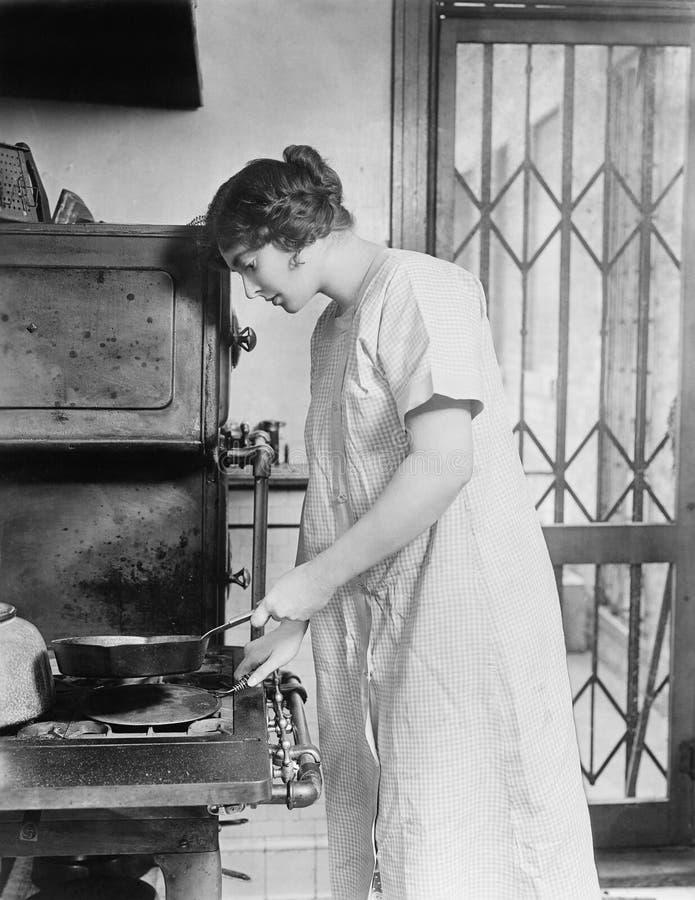烹调在火炉的妇女(所有人被描述不更长生存,并且庄园不存在 供应商保单将有n 免版税库存照片