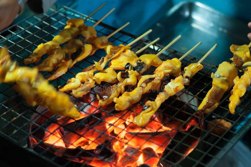 烹调在火炉,泰国烹调传统街道海鲜棍子的烤乌贼手 免版税图库摄影
