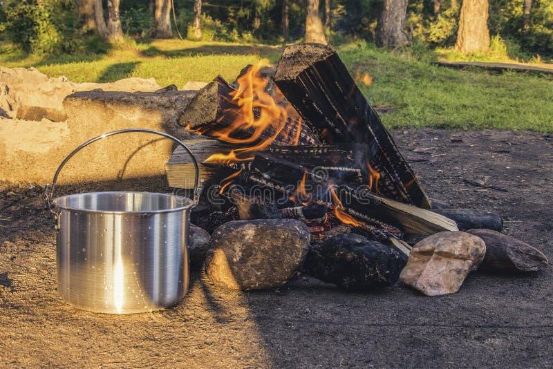 烹调在火的金属平底深锅在森林阵营 休闲 生活方式 免版税库存图片