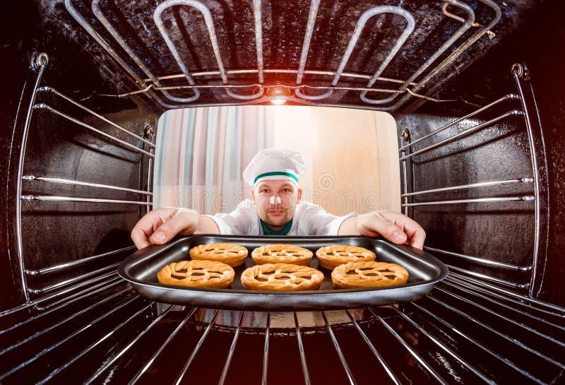 烹调在烤箱的厨师 库存照片