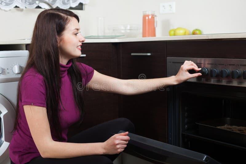 烹调在烤箱的微笑的妇女饼 库存照片