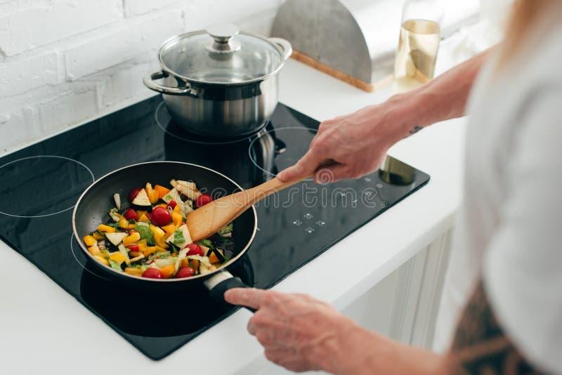 烹调在煎锅的人播种的射击菜在电火炉 免版税库存照片