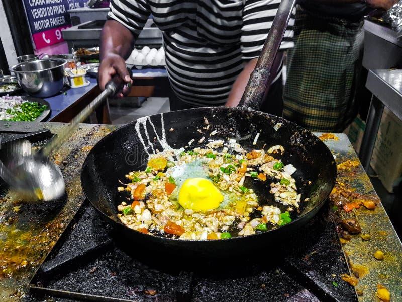 烹调在煎锅的厨师tadka油炸物在一个火炉的一个路边食物角落在火焰 图库摄影