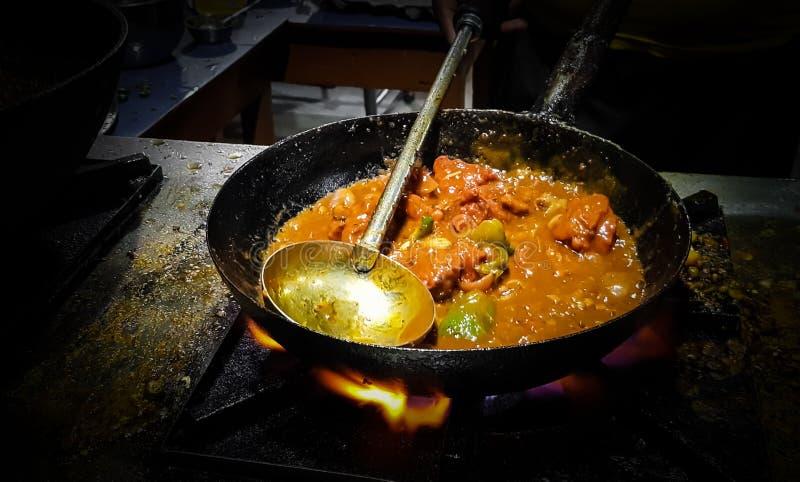 烹调在煎锅的厨师tadka油炸物在一个火炉的一个路边食物角落在火焰 库存图片
