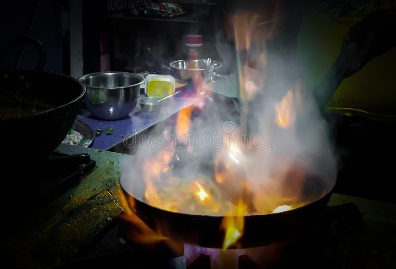 烹调在煎锅的厨师tadka油炸物在一个火炉的一个路边食物角落在火焰 库存照片