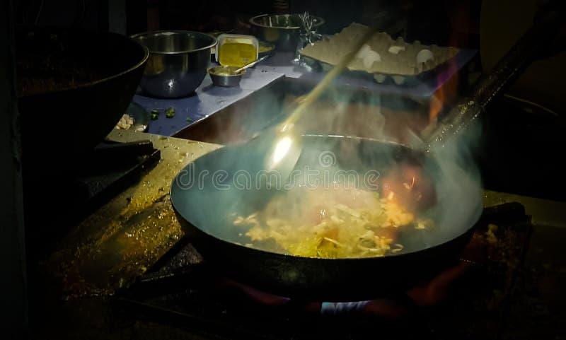 烹调在煎锅的厨师tadka油炸物在一个火炉的一个路边食物角落在火焰 免版税库存照片