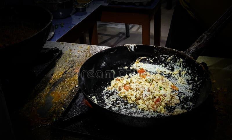 烹调在煎锅的厨师tadka油炸物在一个火炉的一个路边食物角落在火焰 免版税库存图片
