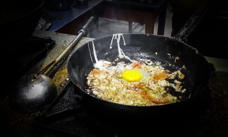 烹调在煎锅的厨师tadka油炸物在一个火炉的一个路边食物角落在火焰 免版税图库摄影