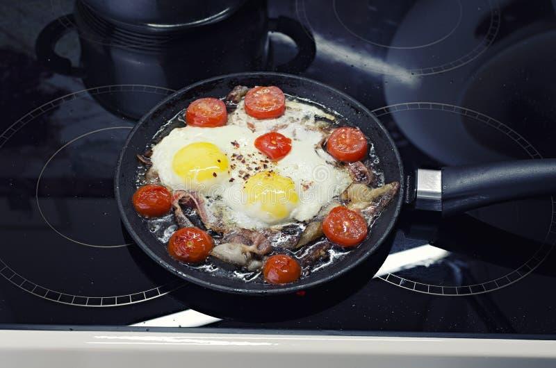 烹调在煎锅的炒蛋,烹调在一个陶瓷火炉、荷包蛋用烟肉和蕃茄,顶视图特写镜头 免版税库存照片