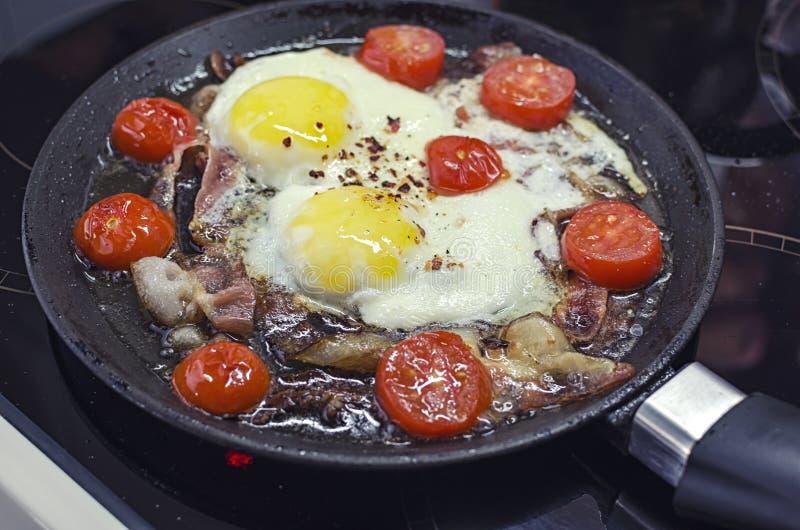 烹调在煎锅的炒蛋,烹调在一个陶瓷火炉、荷包蛋用烟肉和蕃茄,45个看法特写镜头 图库摄影