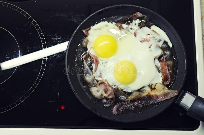 烹调在煎锅的炒蛋,烹调在一个陶瓷火炉,炒蛋用烟肉,顶视图 库存图片