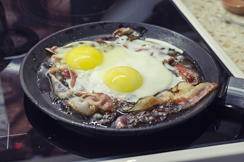烹调在煎锅的炒蛋,烹调在一个陶瓷火炉,炒蛋用烟肉,45个看法特写镜头 库存照片