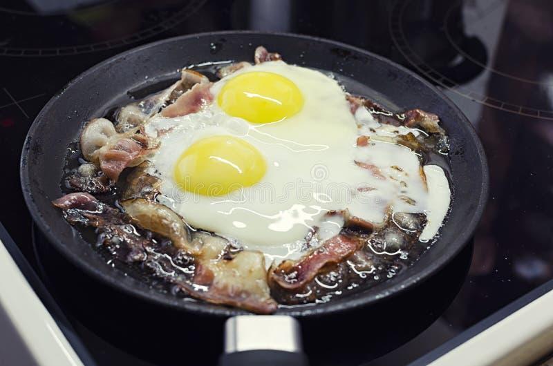 烹调在煎锅的炒蛋,烹调在一个陶瓷火炉,炒蛋用烟肉 免版税库存照片