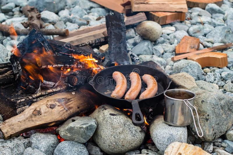烹调在生铁长柄浅锅的香肠在营火,当野营时 好和正面营火食物 库存照片
