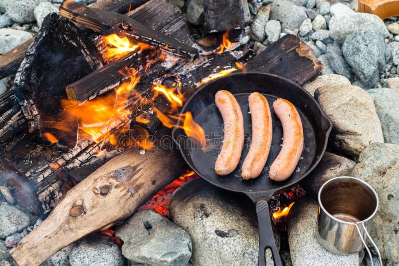 烹调在生铁长柄浅锅的香肠在营火,当野营时 好和正面营火食物 免版税图库摄影