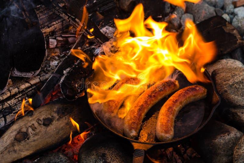 烹调在生铁长柄浅锅的香肠在营火,当野营时 好和正面营火食物 免版税库存图片