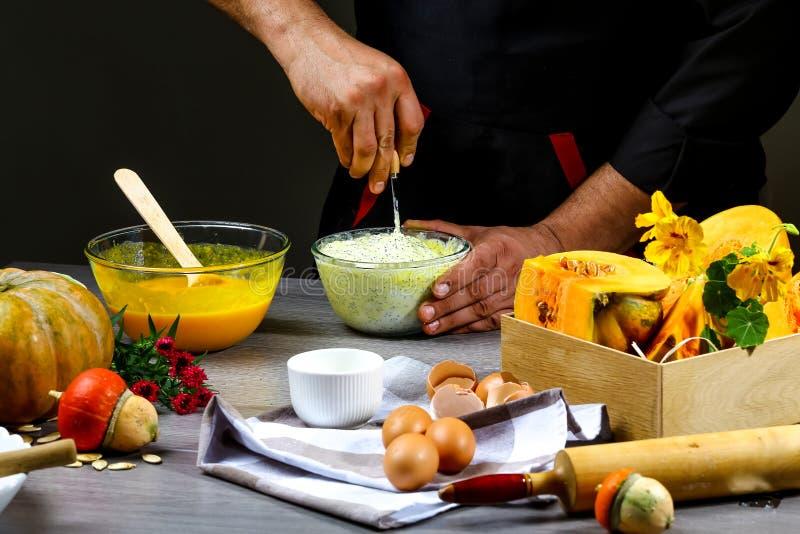 烹调在美国南瓜饼的厨师手面团用桂香和乳酪 在倾吐的餐馆沙拉的主厨概念食物新鲜的厨房油橄榄 库存图片