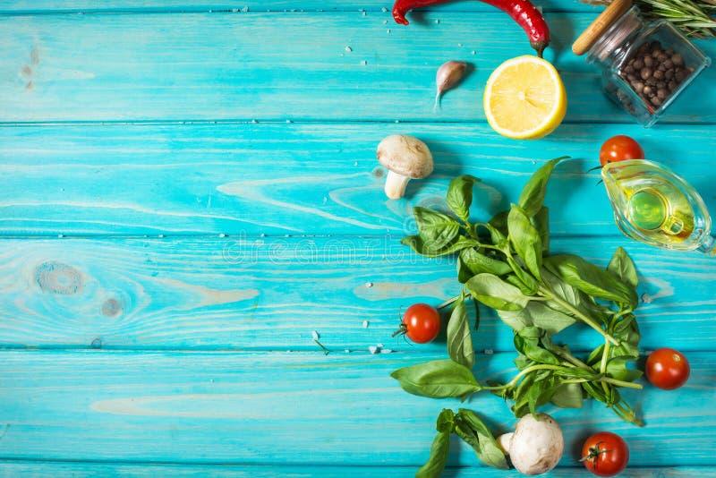 烹调在蓝色木桌上的食物背景 罗斯玛丽、蓬蒿、蕃茄、柠檬,迷迭香和其他 顶视图 库存照片