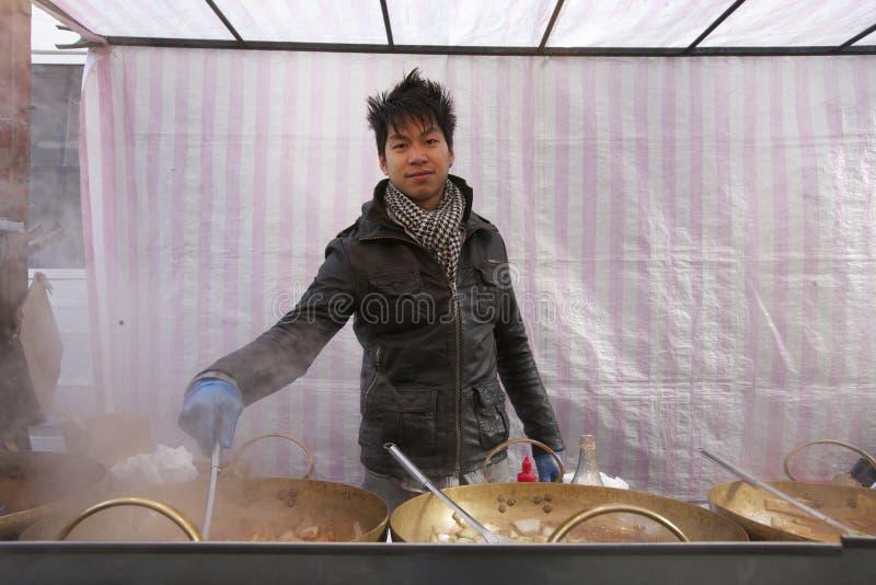 烹调在街道食物摊位的一个年轻亚裔人的画象 免版税库存照片