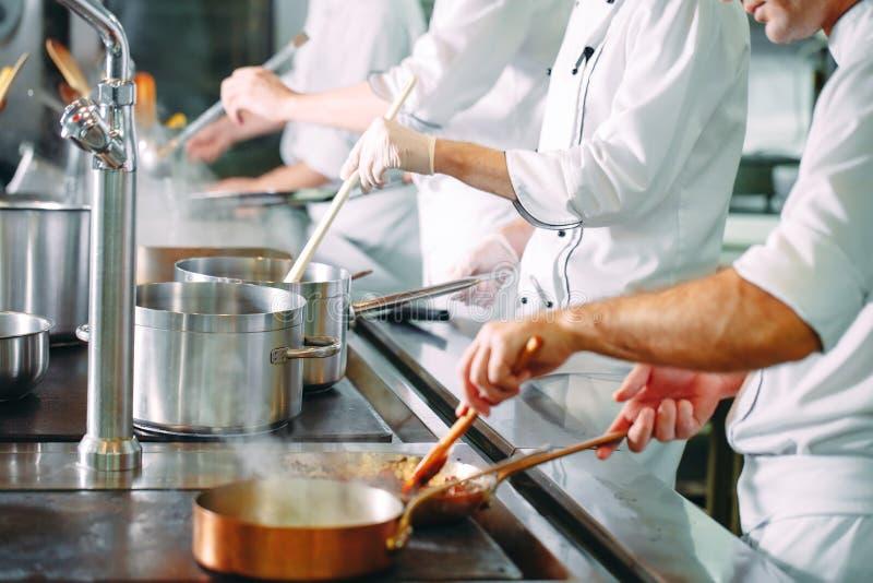 烹调在铁锅平底锅的厨师菜 ?DOF 库存照片