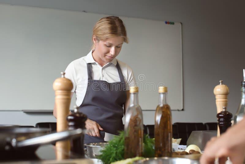 烹调在餐馆厨房里的年轻女人在烹饪课期间 免版税库存照片