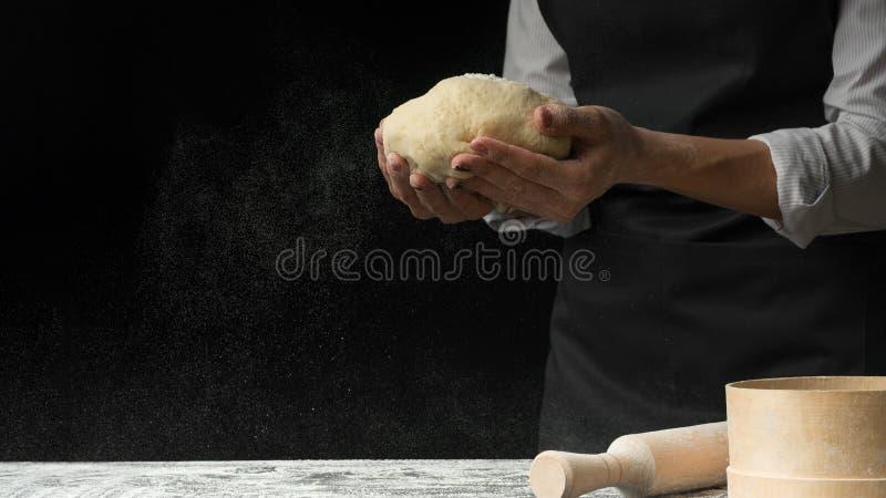 烹调在黑暗的木背景的厨师 营养的概念,烹调面团、比萨和面包店 库存照片