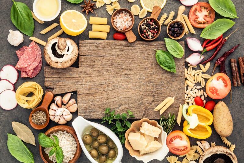 烹调在黑暗的石背景的意大利食物成份与c 免版税库存图片