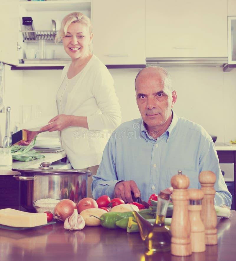 烹调在他们的厨房的愉快的资深夫妇 免版税库存图片