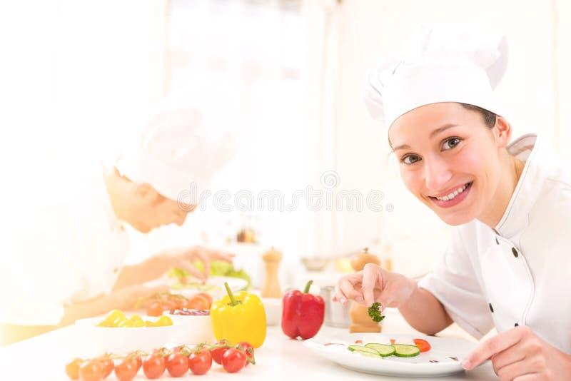 烹调在他的厨房里的年轻可爱的专业厨师 库存照片