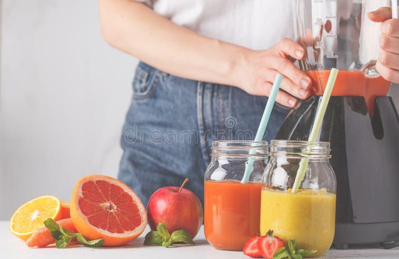 烹调多彩多姿的夏天果汁或圆滑的人在gl的妇女 图库摄影