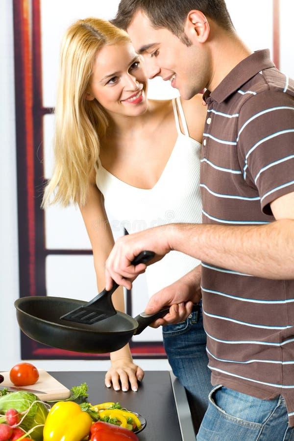 烹调夫妇愉快的年轻人 免版税库存图片