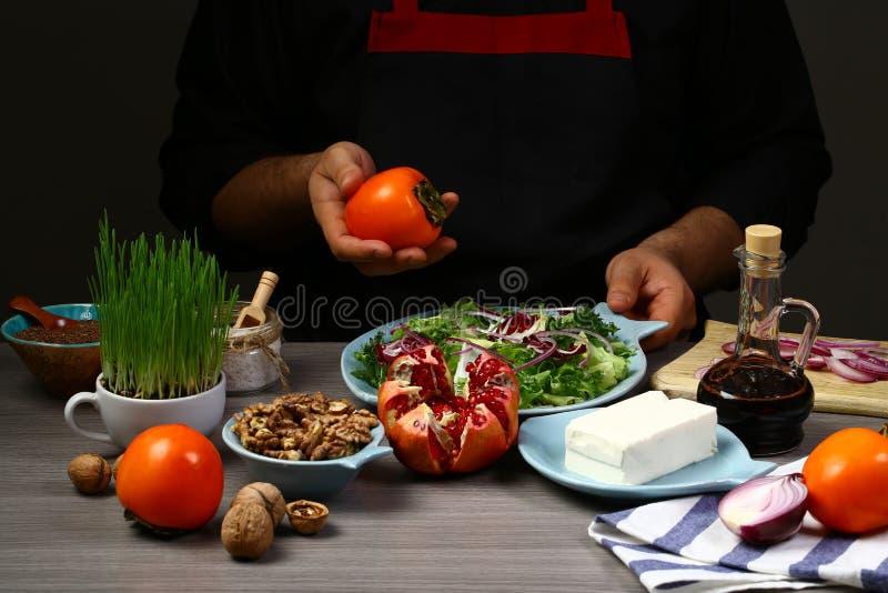 烹调季节性沙拉的厨师手 柿子、鲕梨、石榴和不同的莴苣叶子 库存照片
