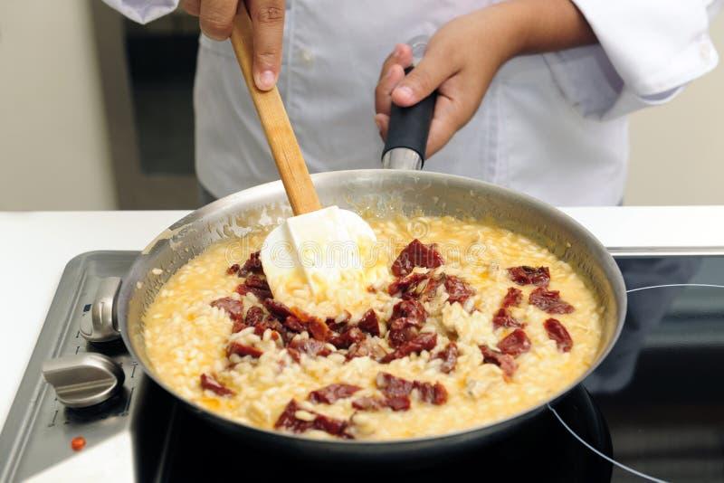 烹调干意大利煨饭蕃茄的主厨 库存图片